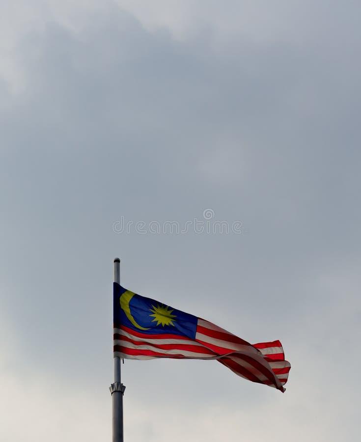 Malaysisk flagga som vinkar i den blåa himlen royaltyfri fotografi