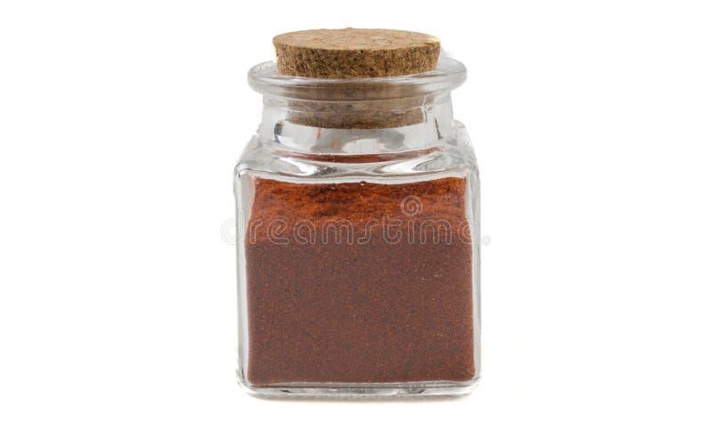 Mald eller jordpaprika eller röd peppar i exponeringsglaskrus på isolerat på vit bakgrund Bekl?da besk?dar Kryddor och matingredi royaltyfria bilder