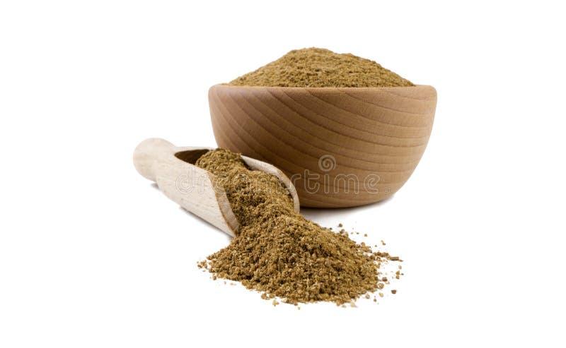 Mald eller mald kummin i träbunke och skopan som isoleras på vit bakgrund Kryddor och matingredienser arkivfoto