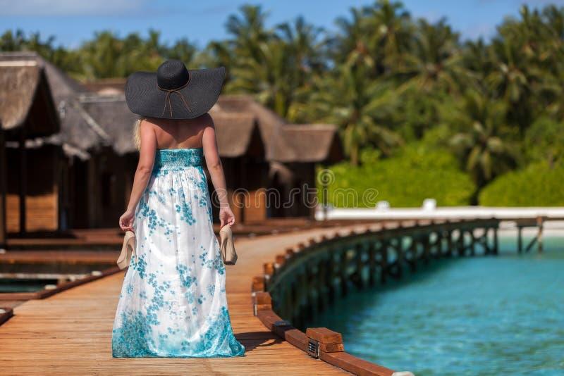 Maldivas, jovem mulher que anda ao longo da ponte com saltos altos na mão e em um chapéu negro imagem de stock royalty free