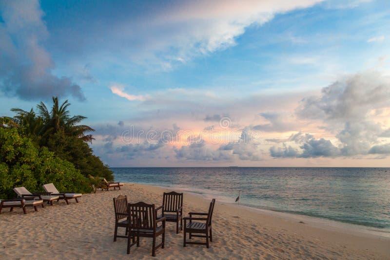Maldivas, paraíso tropical, tabela, cadeiras e vadios na praia, nascer do sol fotos de stock royalty free