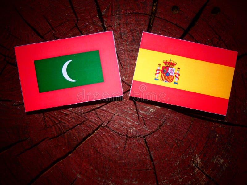Maldivas señalan por medio de una bandera con la bandera española en un tocón de árbol foto de archivo libre de regalías