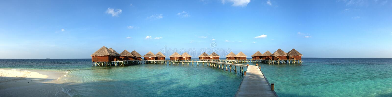 Maldive island resort. Panorama of water bungalows in a lagoon royalty free stock image
