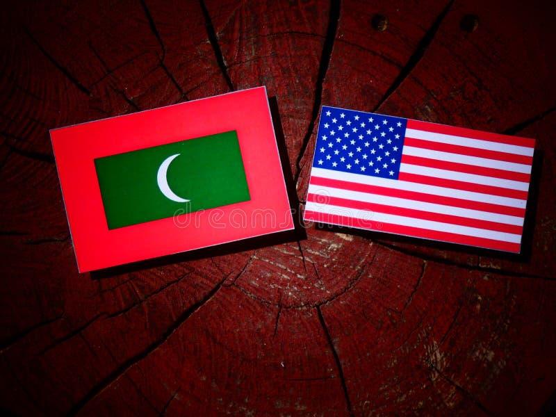 Maldiverna flagga med USA flaggan på en trädstubbe royaltyfri bild