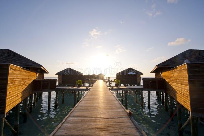 Maldiverna vattenvilla, solnedgång arkivbilder