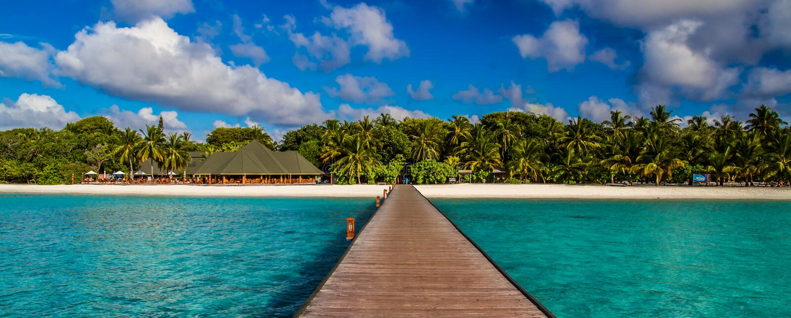 Maldives beach panorama under the blue sky. Maldives beach panorama. Luxury water villas, in exotic blue lagoon. Wide screen background concept. Magical stock images
