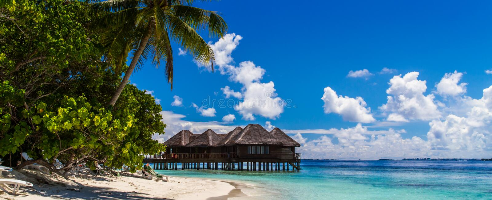Maldives beach panorama under the blue sky. Maldives beach panorama. Luxury water villas, in exotic blue lagoon. Wide screen background concept. Magical royalty free stock photos
