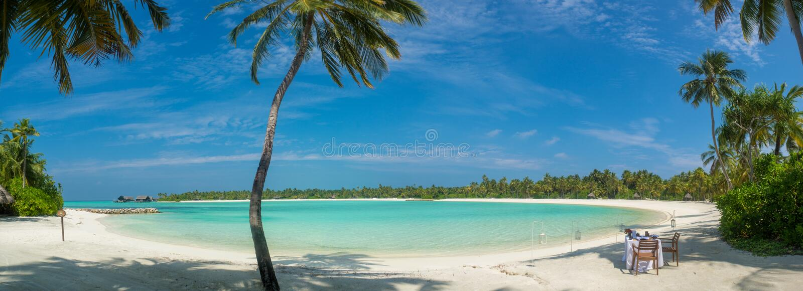 Maldives beach panorama view with breakfast setup royalty free stock photo