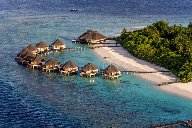 Maldives. A beach scene from Meedhupparu in the Maldives. Water Huts and Beach Villas. Crystal blue sea and white sandy beach with green flora. Reefs also stock photos