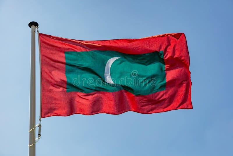 Maldives flagi falowanie przeciw jasnemu niebieskiemu niebu fotografia stock