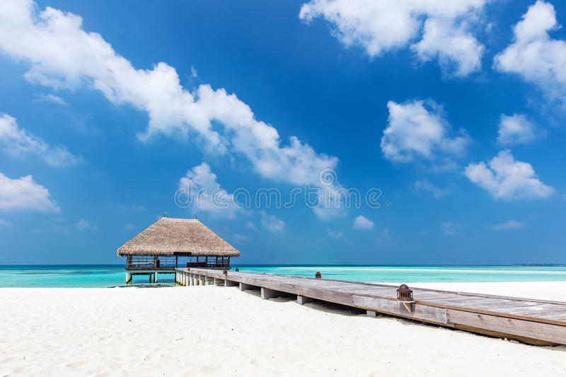 Maldives islands. Wooden jetty with water relaxation lodge. royalty free stock image