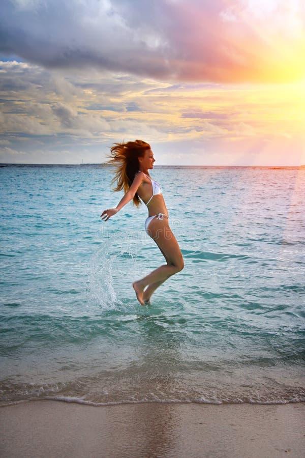 maldives La silhouette que la jeune femme mince saute heureusement en mer sur un coucher du soleil photographie stock libre de droits