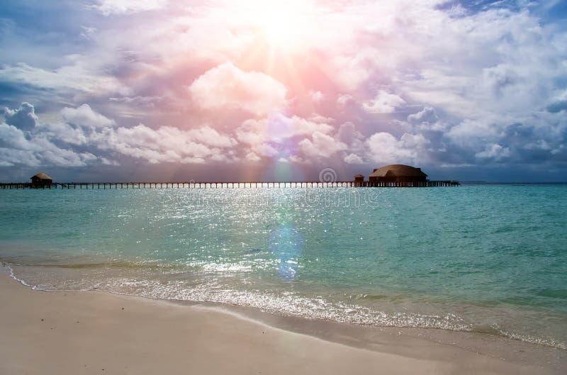 maldives O mar de turquesa na luz do sol e na ponte de madeira sobre a água foto de stock royalty free