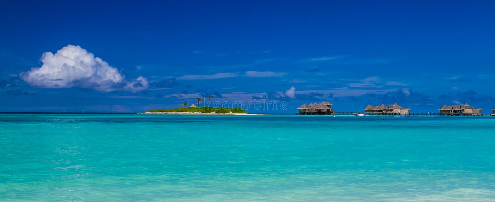 Maldives water bungalows panorama under the blue sky. Maldives beach panorama. Luxury water villas, in exotic blue lagoon. Wide screen background concept royalty free stock photo