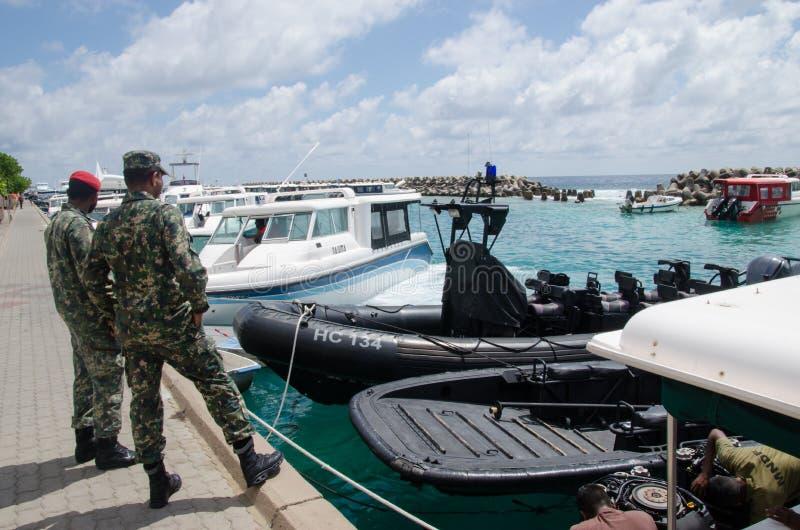 Maldivian στρατιωτικός δύο που στέκεται κοντά στις βάρκες στρατού στοκ φωτογραφία με δικαίωμα ελεύθερης χρήσης