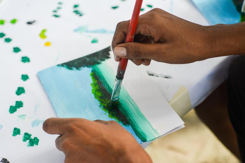 Maldivian artist painting beautiful landscape of tropical island. In Maldives stock images