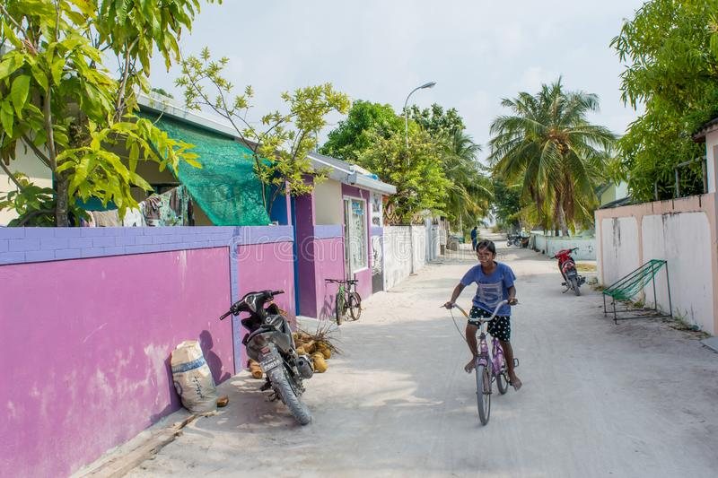 Maldivian boy riding bicycle on the street in the village at the tropical island. Maamigili in Maldives royalty free stock image