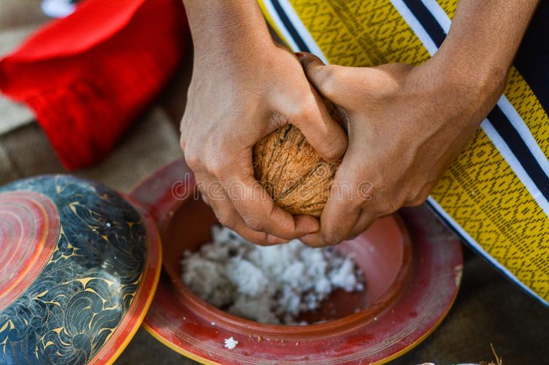 Maldivian girl separating coconut pulp to the plate. In Maldives stock photos