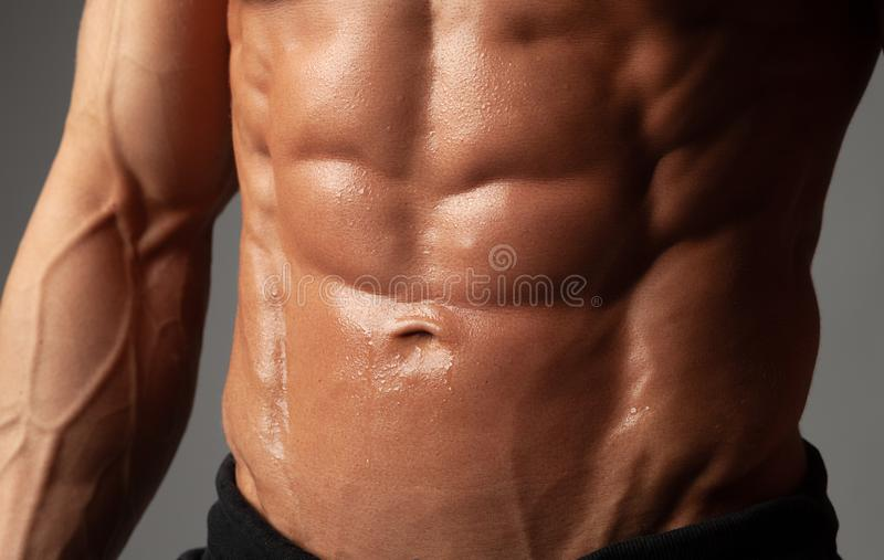 Male abdominal muscles closeup with sweat drops after exercise royalty free stock image