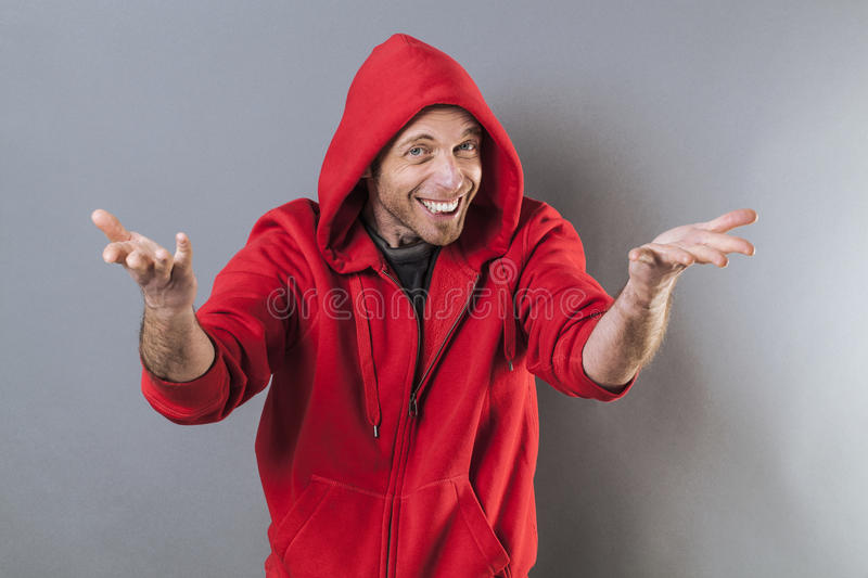 Male adolescence concept,playing rapper. Male adolescence concept - smiling middle age wearing a red hooded sweater playing rapper with fun hand gesture,studio stock images