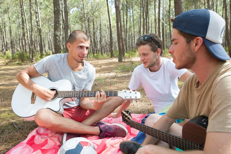 Male adolescents in woods paying guitars. Guitar royalty free stock photos