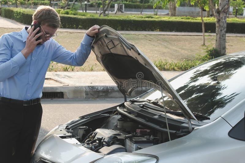 male agent examining engine for claiming auto insurance. caucasian man calling for assistance for car damaged by traffic accident stock images