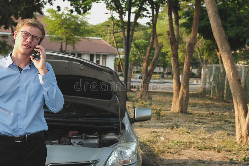 Male agent use smart phone for claiming auto insurance. caucasian man calling for assistance for car broken down by traffic. Male agent use smart phone for stock photography