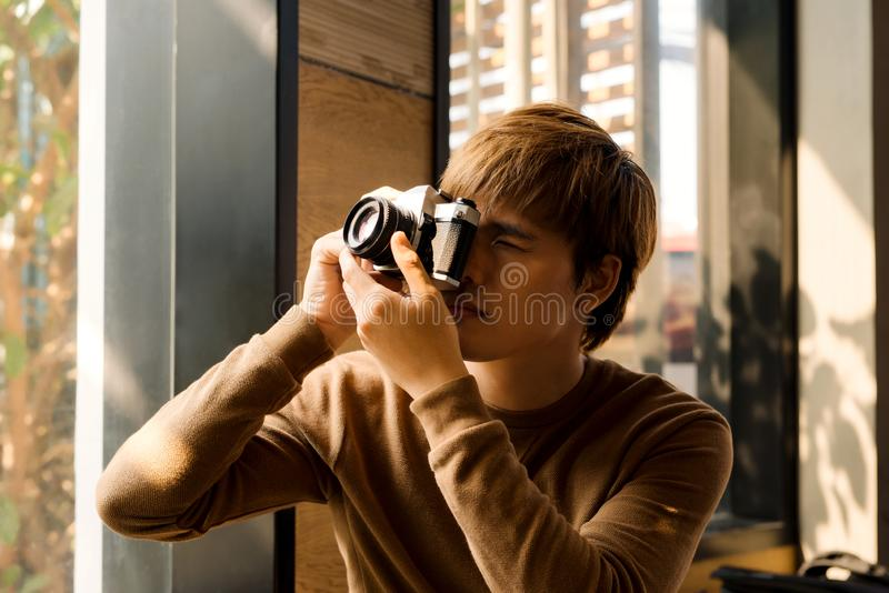 Male amateur photographer in eyeglasses focusing to make photos out of window sitting on windowsill.Young bearded man resting in royalty free stock images