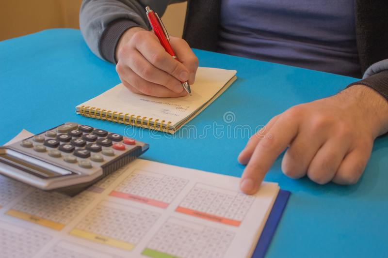Male Analyzing Statistics Financial Concept. Business owners, accounting and technology, business, calculator and documents in the stock image