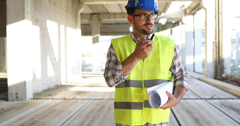 Male architect with blueprints using walkie-talkie stock images