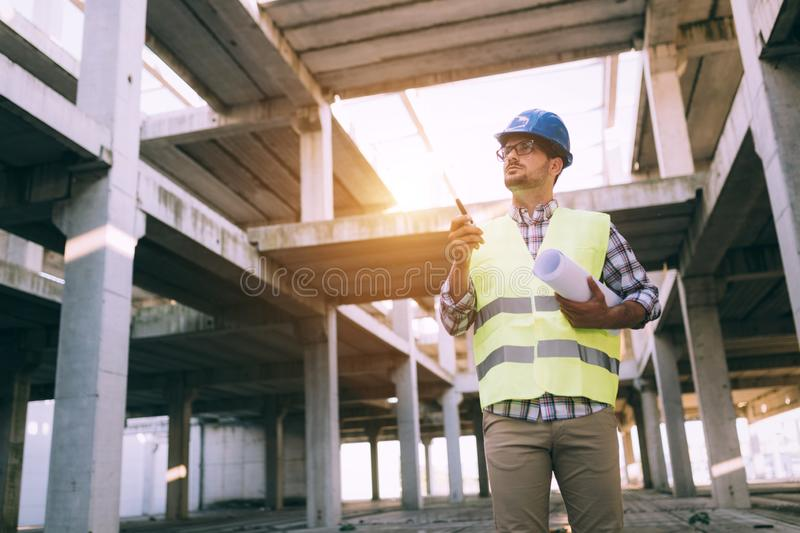 Male architect communicating on walkie-talkie at site. Male architect communicating on walkie-talkie at building site royalty free stock photos