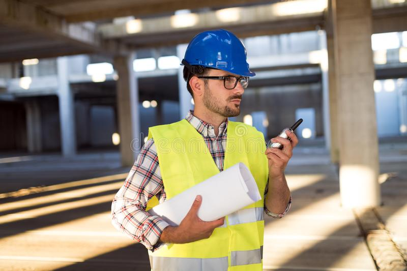 Male architect communicating on walkie-talkie at site. Male architect communicating on walkie-talkie at building site stock image