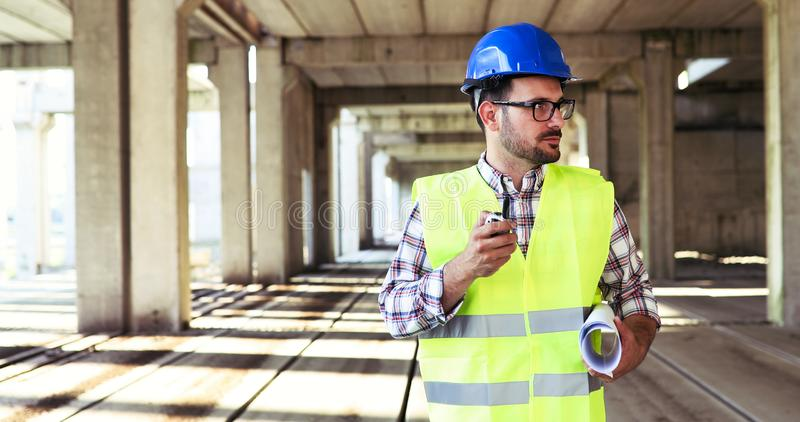 Male architect communicating on walkie-talkie at site royalty free stock photo