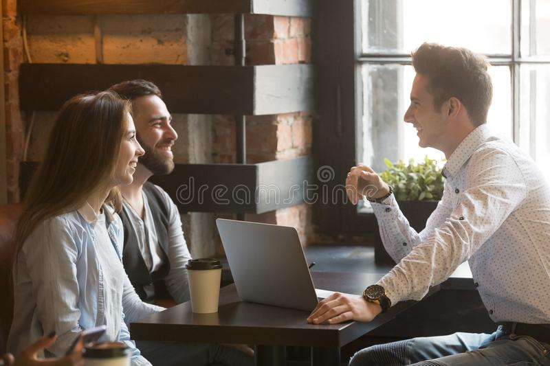 Male architect consulting excited millennial couple in coffee sh. Male architect talking to smiling millennial couple, consulting on housing project, realtor stock images