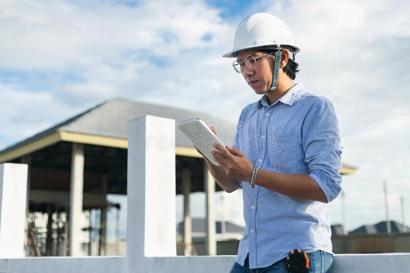 Male architect inspecting building house construction  worker at development site stock photo