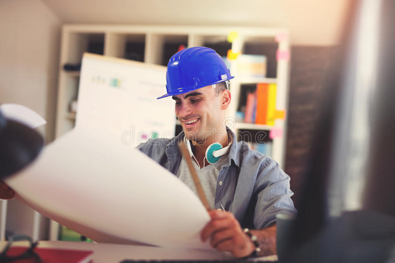 Male architect studying plan. In office royalty free stock photography