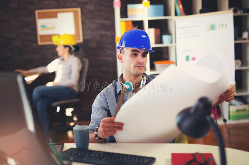 Male architect studying plan. In office stock image
