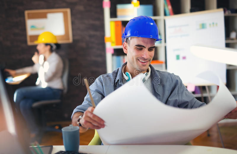Male architect studying plan. In office royalty free stock photo