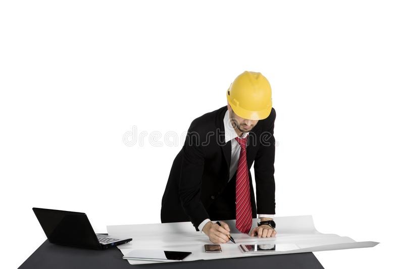 Male architect works on desk with blueprint stock photo image of male architect working on the table with blueprint digital tablet laptop and wearing helmet malvernweather Gallery