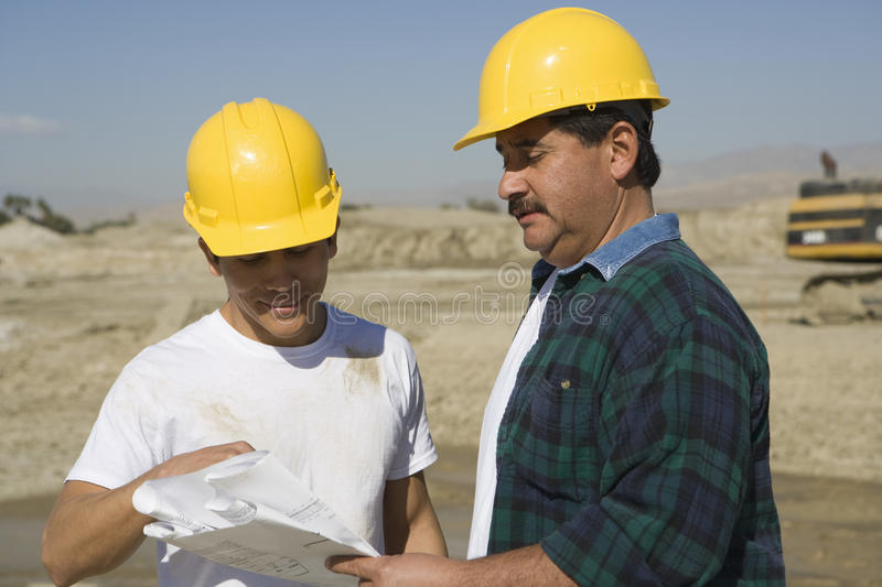 Male Architects Discussing At Construction Site royalty free stock photo