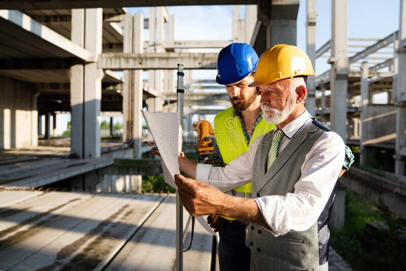 Male architects analyzing blueprint at construction site royalty free stock image