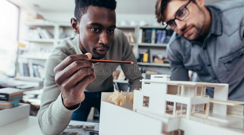 Male architects in office discussing construction project stock photography
