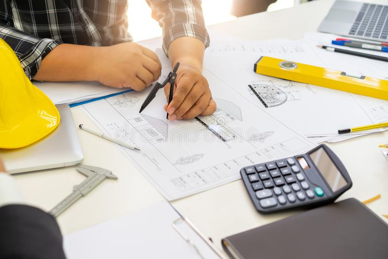 Male architects using divider compass for designing, stock photo