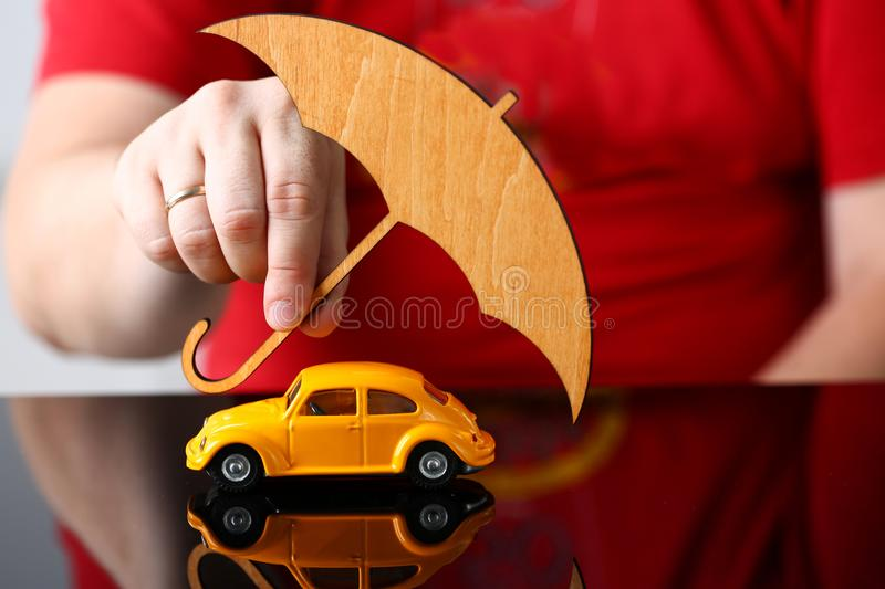 Male arm cover yellow toy car. Male arm cover unrecognizable yellow toy car with umbrella closeup. Driver money loss prevention, parasol, secure road trip, drive royalty free stock photo