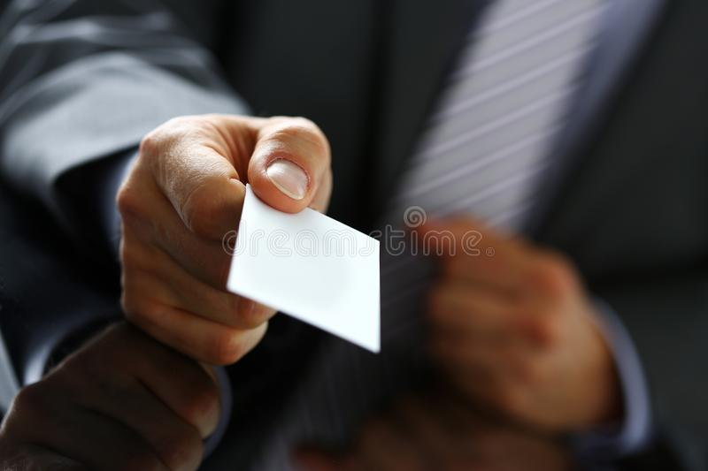 Male arm in suit give blank calling card to visitor. Closeup. White collar colleagues company name exchange, job interview, sale clerk id, executive or ceo royalty free stock photography