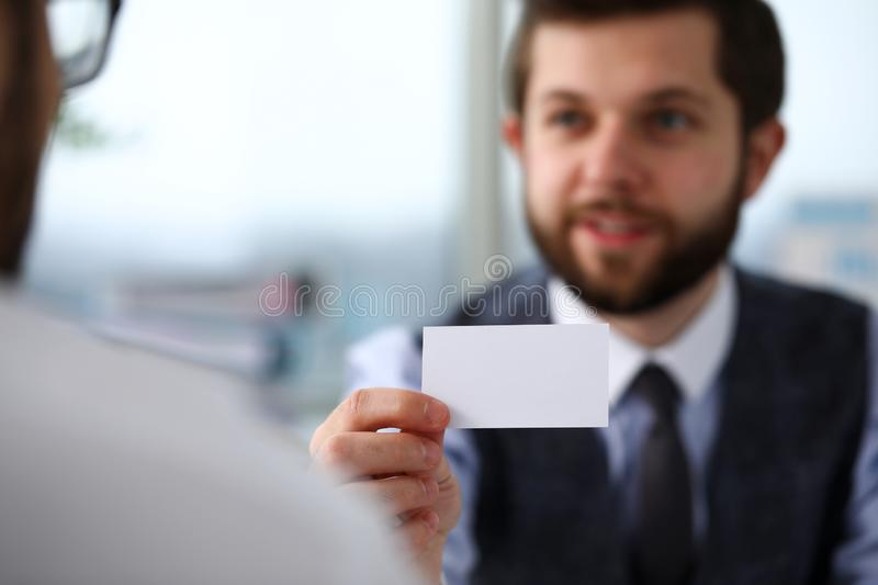 Male arm in suit give blank calling card to visitor. Closeup. White collar colleagues company name exchange job interview sale clerk id executive or ceo finance stock image