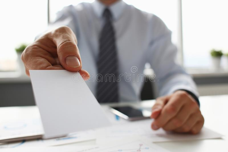 Male arm in suit give blank calling card to visitor. Closeup. White collar colleagues company name exchange job interview sale clerk id executive or ceo finance stock photography