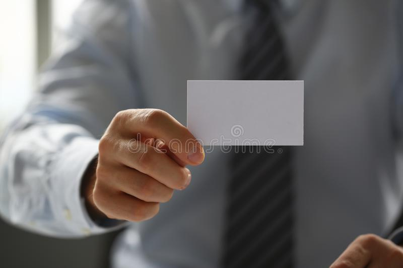Male arm in suit give blank calling card to visitor. Closeup. White collar colleagues company name exchange job interview sale clerk id executive or ceo finance royalty free stock images