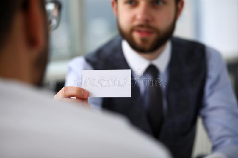 Male arm in suit give blank calling card to visitor. Closeup. White collar colleagues company name exchange job interview sale clerk id executive or ceo finance stock photos