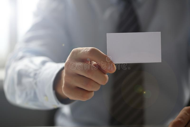 Male arm in suit give blank calling card to visitor. Closeup. White collar colleagues company name exchange job interview sale clerk id executive or ceo finance royalty free stock image